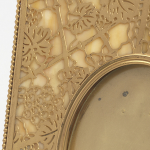 Of upright rectangular form, the gilded metal surface cut in the grapevine pattern overlaid on a panel of pearly-hued Favrile glass; oval well in center for picture, clear glass oval panel inset in well.  Rigid, hinged gilt-wire support on reverse.