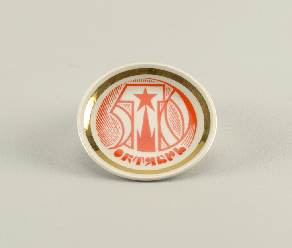 "Circular, painted in bright orange with a stylized ""50,"" a tower with star finial, and the inscription (in Russian) ""October; gilded border."