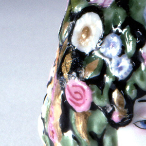 Face of woman with floral hair/headdress on each side, one with eyes open, one with eyes closed