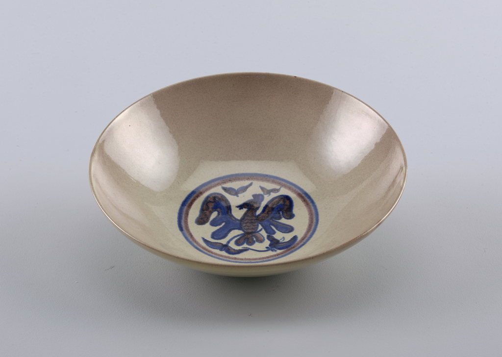 """The broad bowl rests upon a circular foot rim; the side walls curve outward toward the lip.  Both exterior and interior are glazed in a softly mottled grey-green and mauve.  In the center of the bowl is underglaze cobalt blue and manganese purple design of a stylized bird with wings spread, between foliage elements.  The design is encircled by a double blue and purple circular band.  On the unglazed underside of the bowl is incised the signature """"Scheier""""."""