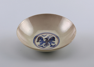 "The broad bowl rests upon a circular foot rim; the side walls curve outward toward the lip.  Both exterior and interior are glazed in a softly mottled grey-green and mauve.  In the center of the bowl is underglaze cobalt blue and manganese purple design of a stylized bird with wings spread, between foliage elements.  The design is encircled by a double blue and purple circular band.  On the unglazed underside of the bowl is incised the signature ""Scheier""."