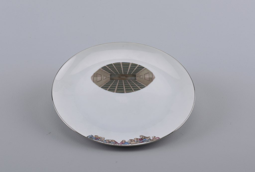 "A white plate with a photo decal in the shape of an eye of a pupil reflex. Along the bottom edge of the plate there is a second photo decal of the table and people from ""The Last Supper""."