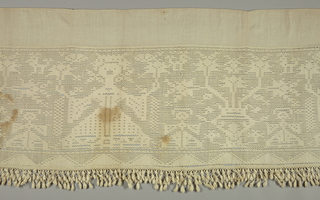 "Valance of white linen patterned by open weaving also known as ""red de telar"" or ""red de Val de Verdja."" Design shows a central female figure holding candles and flanked on either side by large-scale stylized vase form with flowers. In the interstices are small-scale female figures and animals. Heavy fringe on the bottom and band of plain linen at top."