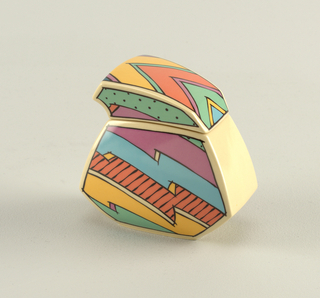 Playful six-sided jagged-shaped sugar bowl and lid in bright colors of pink, orange, yellow, green and blue with bold black outlines of jagged shapes, checkerboard, dots, and lines. Lid is asymmetrical and when placed on top of bowl matches exact design pattern of color.