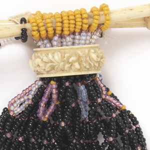 Purse of black beads strung in an open diamond-shaped pattern with white and gold beads as decoration. Carved ivory or bone ring to slide and close purse. Two small ivory bars at top through last row of beads, to open. Small chain of black and white beads for carrying. Corner tassels of pink beads.