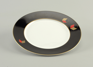 Dish with bright white well; border in black with gilt rim, and three three-dimensional cubes in gold, red, and black; two on one side and one on the other.