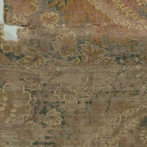 Very long narrow vertical symmetrical repeat of floral forms with long spreading and enclosing leaves and some filling decoration. In white, dark green, rust, pink, and dark golden tan wool pile formed by extra pile warps on a ground of very dark linen. Several dark plain cloth selvages.