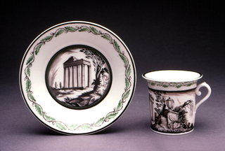 Cup cylindrical with flaring lip, scroll handle with palmette motif at base; painted around sides in grisaille with scenes of classical architecture and garden ruins; green oakleaf border at top. Saucer circular with raised edge; painted in the center with scene of classical temple ruins, trees, figures, with a green oakleaf border