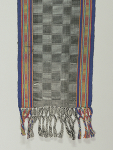 Sash with a center section in a checkerboard-like pattern of black and white squares. Multicolored borders of narrow stripes in blue, red and green. Knotted warp fringe at either end. Heavy ribbed effect.