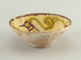 Red earthenware bowl with visible throwing rings. Thick round foot. Traces of slip on exterior. Interior rim painted with a rust-colored line. Interior of bowl painted with profile of a bird in rust, with wings, eyes and long, curling feather in yellow over red. Repairs.