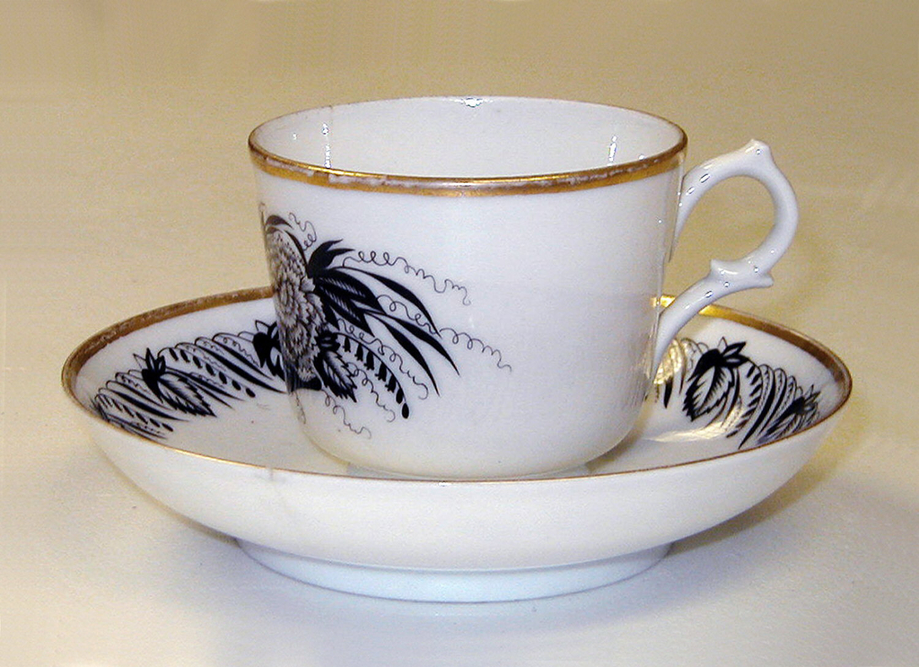 Cup with slightly flaring sides, loop handle, painted with image of a rose and a carnation in black, gilded rim top edge; saucer circular with gilded rim and border of leaves