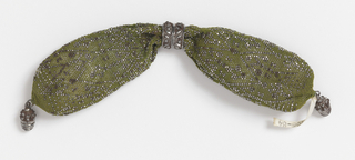 Crocheted silk of yellowish-green is ornamented with cut steel beads in double zigzag and diamond patterns. Steel rings with relief pattern control side opening; ornate acorn-shaped drops at each end.