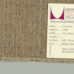 Plain weave with a black and tan warp and brown weft. Warp is comprised of fine lightweight threads while the weft is a coarsely woven heavier yarn. The two colors of the warp produce a subtle vertical stripe effect.