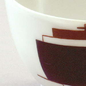 In the shape of a cup sliced in half through the middle, with applied flat solid square handle; both round side and flat side of cup painted with Suprematist decorations composed of black and reddish-brown geometric shapes floating on white background.