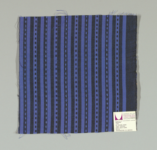 Blue and black narrow vertical stripes with small blue and black rectangles. Rectangular patterning is formed by supplementary warp floats. Number 1320.