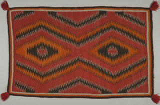 Rug in a zigzag pattern of red, black, white and orange. Zigzags create a large scale diamond pattern. Red wool tassel in each corner.