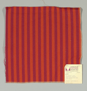 Warp-faced twill in vertical stripes of orange and dark red. Plain weave binding foundation has light brown warp and weft threads.