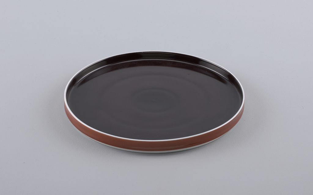 Flat circular form with slightly concave upright rim; white body glazed brown on interior, cinamon-brown on exterior rim.