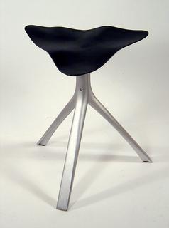 Rippled triangular black iron seat mounted on matt silver-colored aluminum tripod base.