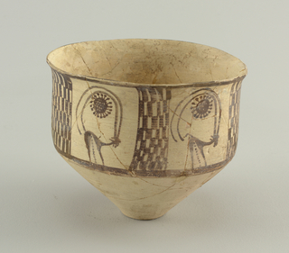 Lower part of vessel is conical with small foot. Sides strait, slightly flaring rim. Four rectangular panels with vertically protracted checkerboard pattern alternate with four ibex with long curving horns encircling a sun.