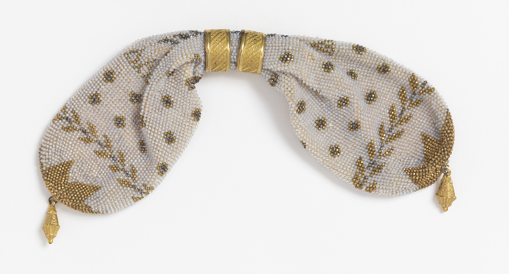 "Initialed ""AC"" and ""JC""; a base of cream-colored knitted silk is solidly covered with minute opalescent beads; it is further ornamented with gold and cut steel beads in a stylized leaf pattern and a pattern of small rosettes. Two gold rings control side opening; small gold drops at either end."