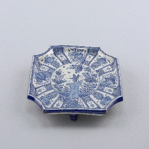 """Flat 8-sided tray with raised rim, on three flattened ball feet; painted in underglaze blue on white with center roundel showing dragonfly, rocks, flowers, surrounded by 8 panels painted with """"precious objects"""" alternating with flowers; feet painted blue."""