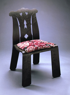 """Wide, flat brown plywood frame, the shape reminiscent of the Chippendale style, with back pierced to form rails and splat; seat upholstered with square wool-upolstered pad in the """"Tapestry"""" pattern of a red, black and white abstracted floral motif."""
