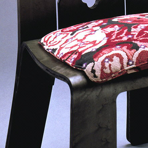 "Wide, flat brown plywood frame, the shape reminiscent of the Chippendale style, with back pierced to form rails and splat; seat upholstered with square wool-upolstered pad in the ""Tapestry"" pattern of a red, black and white abstracted floral motif."