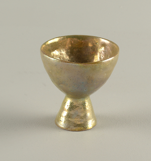 Tall circular goblet of hemispherical shape supported on flared circular hollow foot. Lustre glazed; interior of foot unglazed.