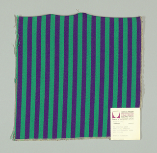 Warp-faced twill in vertical stripes of green and violet. Plain weave binding foundation has light brown warp and weft threads.