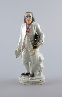 Statuette of Benjamin Franklin standing before a tree-stump, holding a tricorne hat against his left hip, a document in his right hand. Clothing is white with details in gold; a red scarf at his neck. A round base with the gilded inscription: The old English Gentleman