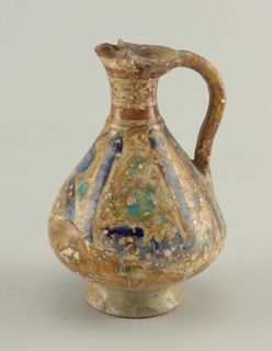 On flaring foot, a pyriform body, contracting to narrow neck with rim compressed to form spout.  Loop handle.  Greenish glaze with brown iridescent and turquoise filling areas between large Kufic letters.