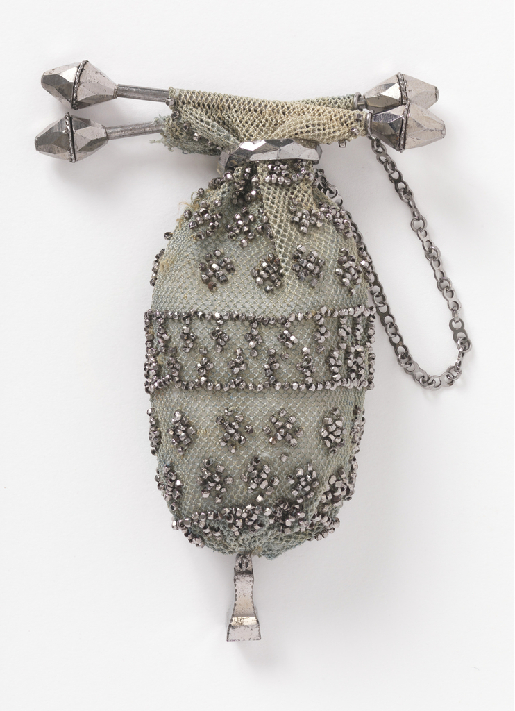 Fine grey silk crocheted net with cut steel beads; steel bars, ring, and chain at top. Pendant ornament of cut steel at bottom.