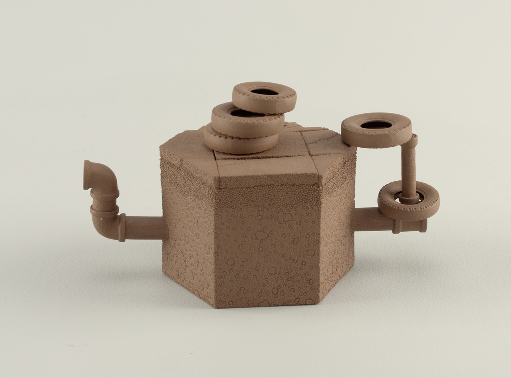 Teapot fabricated entirely of unglazed dark brown stoneware, as in manner of I-Hsing wares. Flat-based octagonal body (a); upright sides modeled to resemble cross-section through concrete street and sidewalk, with indented brickwork niche at one side. Upper surface of body flat, modeled as section of street, with curb, sidewalk, and partial sewer cap. handle formed as square sewer pipe, joined at top with simulated automobile tires, with another tire hanging loose on handle. Spout formed as angled sewer pipe. Inset cover (b) with three stacked tires.