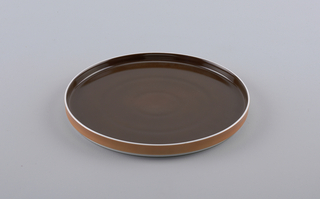 Flat circular form with slightly concave upright  rim; white body glazed brown on interior, orange on exterior rim.
