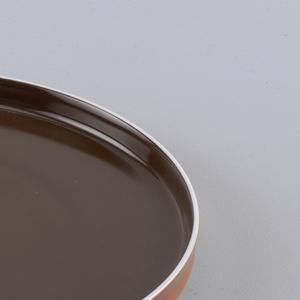 Flat circular form with slightly concave upright  rim; white body glazed brown on interior, orange on exterior rim.