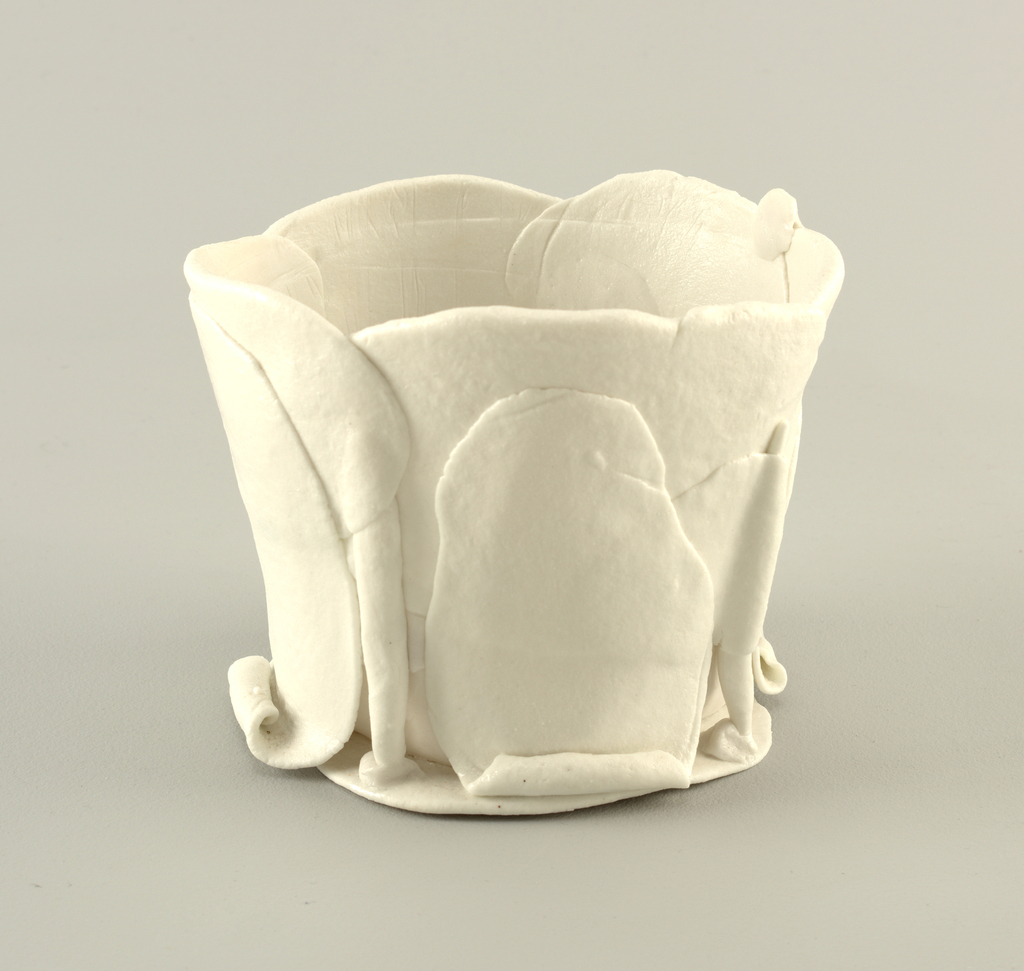 Roughly cylindrical form with undulating mouth, the clear-glazed white body constructed of irregular flat and curled slabs roughly joined and overlapping to create a wall and floor of varying thickness and translucence.