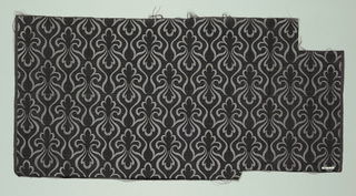 Black and gray fabric with horizontal ribs and an allover modified fleur-de-lys pattern connected by serpentine lines.