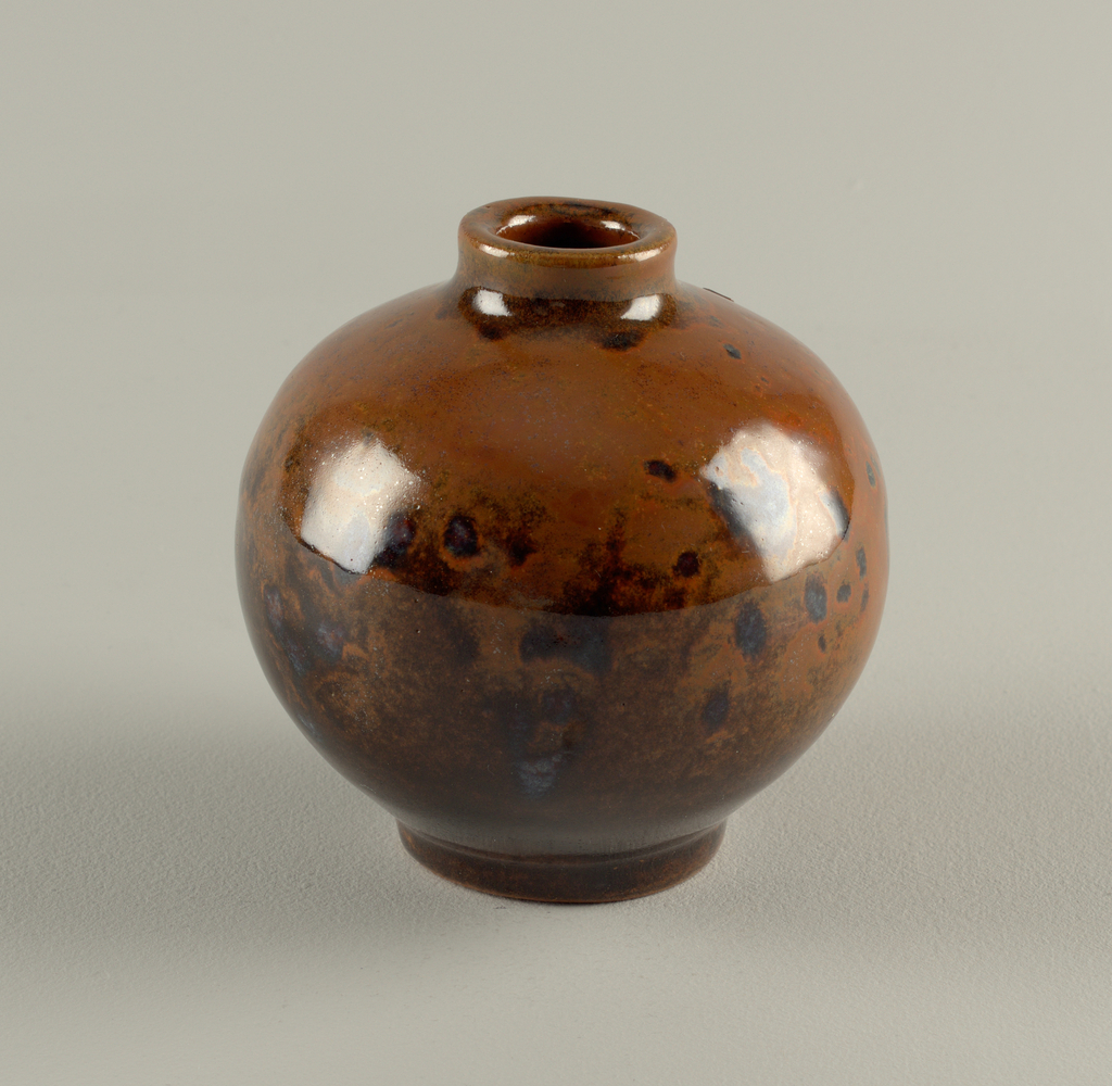 Spherical vase with short straight foot and neck.  Nut brown, glossy glaze over dark Albany slip, reddish brown on top and blackish on lower part.  Slight imperfection on upper part ground down to body.
