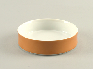 Circular form with upright concave rim; white body with orange glaze on exterior.