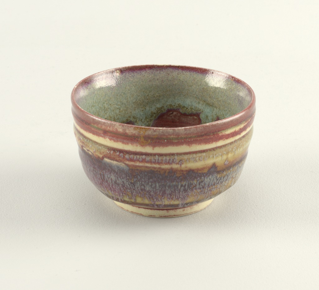 Footed bowl with straight sides; surface with textured horizontal striations; glazed in tones of oxblood red, purple, brown, and light green.