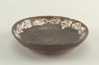 Slightly curved bowl of red clay, with grog added to give coars surface.  Brownish black, metallic glaze, short and dry on outside.  Fourteen streamer-like white trianges with black stripes around inner edge.  Incised spiral line in bottom.