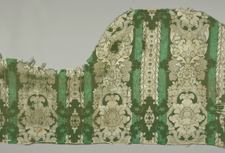 Irregularly cut pieces possibly intended for a sofa in bright and dark green and white. Large-scale design shows stylized symmetrical leaf and flower motifs within broad vertical stripes which are separated by bright green stripes containing arabesques and row of cabuchon forms in dark green and white.