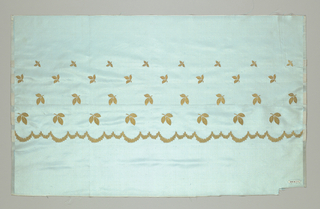 Light blue taffeta fabric with a border design of a scalloped line and leaves in metallic gold thread. There are four rows of leaves that are graduated in size with the largest leaves closet to the scalloped line.