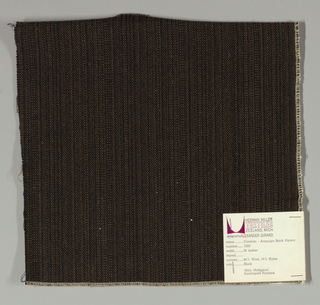 Plain weave with black and brown warp and black weft. Warp is comprised of fine lightweight threads while the weft is a coarsely woven heavier yarn. The two colors of the warp produce a subtle vertical stripe effect.