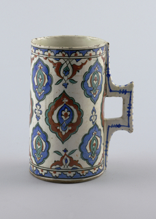 Cylindrical, with cut slab handle running top to bottom on one side. Large all-over diamond-shaped motifs repeat around middle, narrow patterned bands at top and bottom. Buff clay with overglaze, painted green, blue, and terra-cotta.