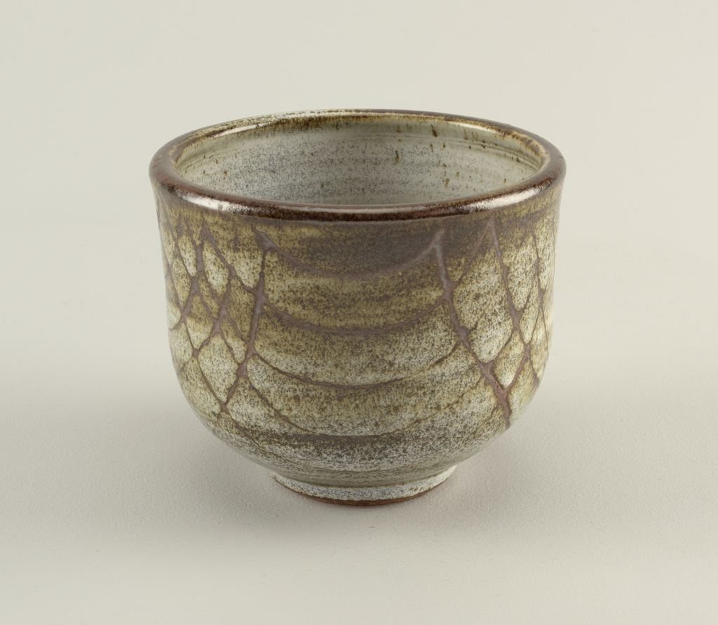 Open bowl with vertical sides, decorated with sgraffito curved lines crossing each other, on mottled greenish glaze. Inside white with speckles.