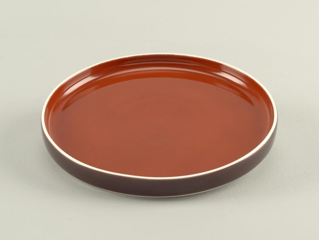 Flat circular form with slightly convex upright rim; white body glazed cinnamon-brown on interior, brown on exterior rim.