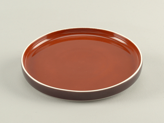 Flat circular form with slightly convex upright rim; white body glazed cinnamon-brown on interior, brown on exterior rim.