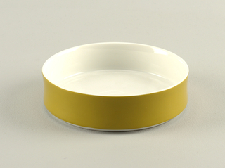 Circular form with upright concave rim; white body with light green glaze on exterior.